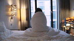 Rear View of a Person Sitting Up in Bed Wrapped in a Blanket Live Action