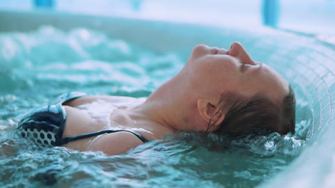 Middle-aged woman in jacuzzi. She is relaxed and enjoys Footage