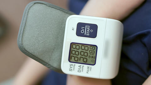 A woman herself measures blood pressure, a blood pressure monitor. Close-up Live Action