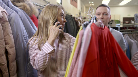 woman talking at cellphone in wholesale shop holding in hands new collection Live Action