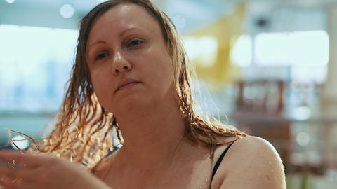 Portrait of a tired middle-aged woman. She is in aqua park with wet hair Live Action