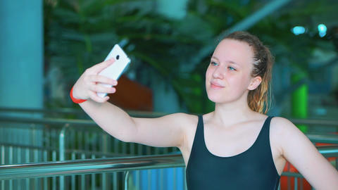 A young girl in a black bathing suit makes a selfie in a public aqua park ビデオ