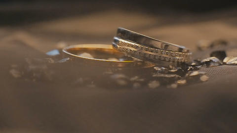 Wedding rings on a decorated surface shining with light close up macro Footage