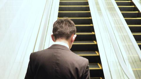 Japanese businessman taking the escalator Live Action