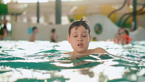 Boy teenager in the water in a public indoor swimming pool aqua park Footage
