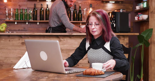Zoom in shot on mature businesswoman in her 40s working on laptop GIF
