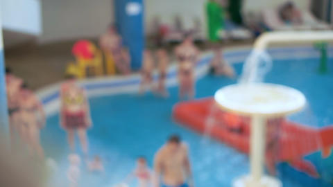 Unfocused view. Children and parents have fun in the children's water park Footage