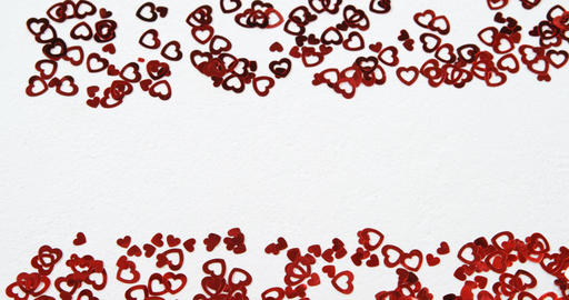 Red heart shape confettis on white surface 4k Live Action