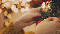 Hand of woman decorating Christmas tree with Christmas glow lights Footage