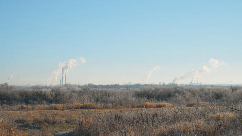 Modern landscape with factory pipes at a distance from which smoke is polluting Footage