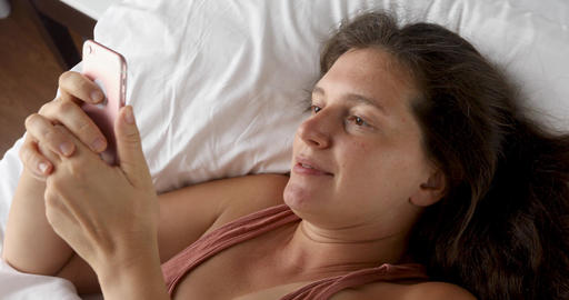 Pretty woman lying looking at phone Footage