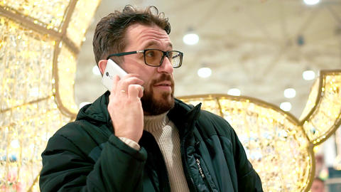 Bearded man in glasses is talking on a smartphone Live Action