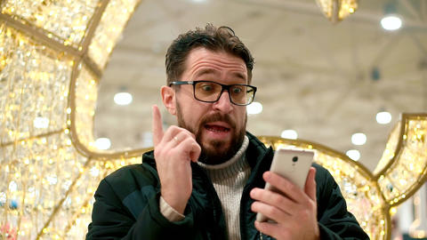 Bearded man with glasses, looks into the smartphone and…, Live Action