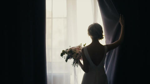 Beautiful bride with bouquet opens a curtain. Silhouette. Focus panorama 영상물
