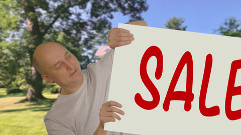 Adult man showing poster with inscription sale on country house background Live Action
