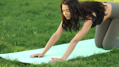 Woman practicing yoga outdoors in park Live Action