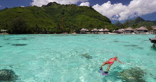 Vacation travel - woman swimming in on beach clear water relaxing on her back Live Action