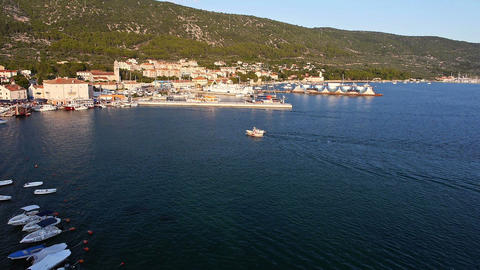 Aerial - Two boats coming back to marina in a seaside town Footage