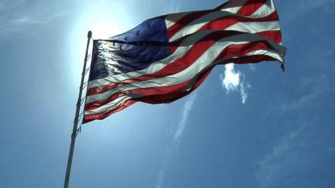An American flag flies against a blue sky Footage