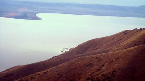 Aerial shot of red mountains alongside a lake in Utah with lens flare Footage
