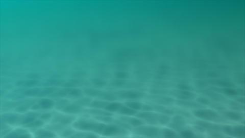 Sunbeams pierce an aqua blue sea, illuminating a sandy seabed Footage