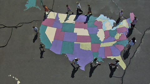 Aerial shot of children walking around a painted USA map on the floor in Utah Footage