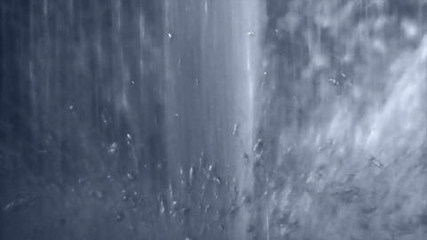A vertical fountain gushes water amidst a circle of water droplets Footage