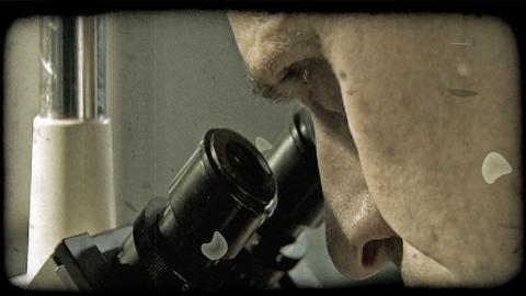 Man looks into microscope. Vintage stylized video clip Footage