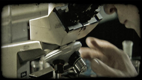 Man positions plate and looks into microscope. Vintage stylized video clip Footage