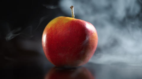 Juicy red apple on dark background in steam Footage
