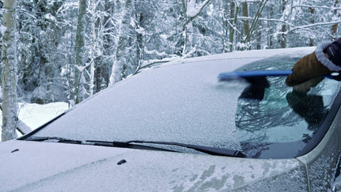 Cleaning snowy car windshield with brush Live Action
