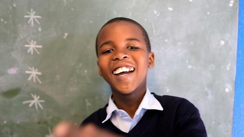 Schoolboy looking at camera in classroom at school 4k Live Action
