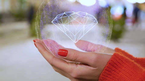 Female hands holding a conceptual hologram with diamond Footage