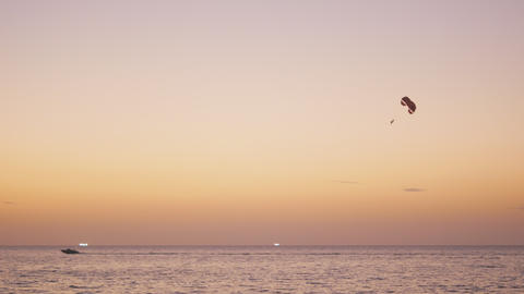 Parachute activity0 at tropical beach after sunset, shot of boat towing Footage