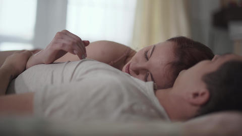 Happy couple talking and smiling, lying in comfortable bed in the morning close Footage