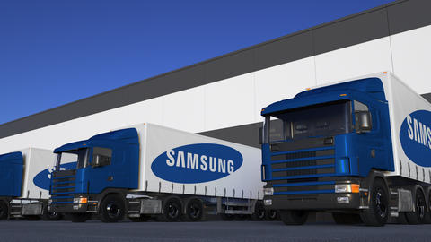 Freight semi trucks with Samsung logo loading or unloading at warehouse dock Footage