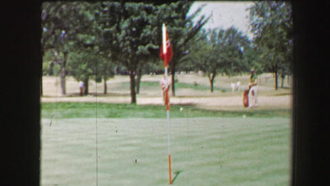 1968: Left handed man hitting golf ball from sand trap onto green near pin hole Footage