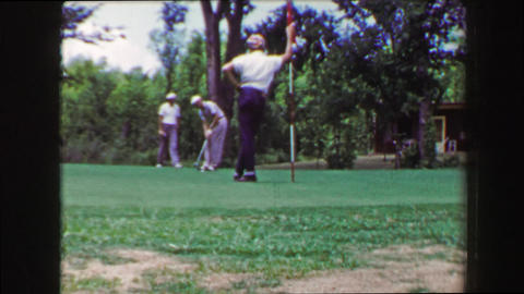 1968: Man long golf putt caddie tends pin ball comes up short Footage