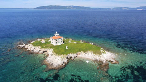 Aerial - Solitude lighthouse with green field and clear blue water around Footage