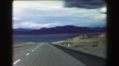 1968: Car driving across open space mountainous mirage dry lake ahead Footage