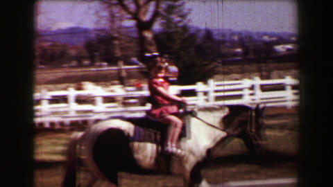 1957: Young girl riding horse at farm petting zoo white picket fence stables Footage