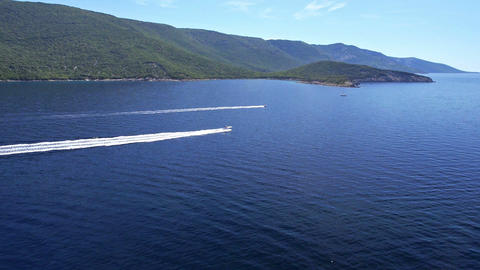 Aerial - Two speedboats sailing on water by the coast Footage