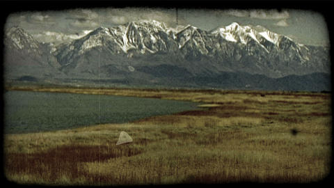 Mountains, lake and dried grasslands. Vintage stylized video clip Footage