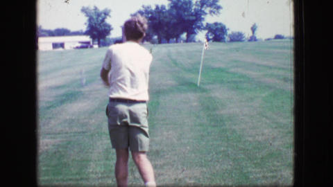 1969: Sideburns young man hits golf balls swing analysis towards practice pin Footage