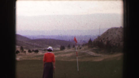 1967: Woman golfer putting on green windy day overlooking hazy valley Footage