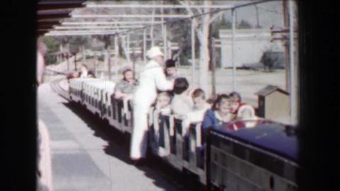 1968: Griffith Park Railroad conductor loads mini train kids into recreational r Footage