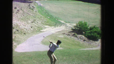 1968: Woman driving golf ball uphill on amazing natural desert landscape course Footage