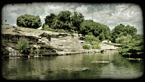 Quiet pond and waterfall in park. Vintage stylized video clip Footage