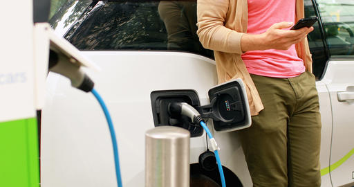 Man using mobile phone while charging electric car at charging station 4k Live Action