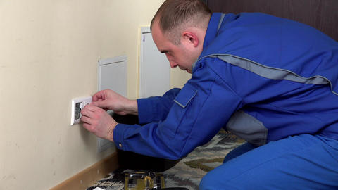 electrician man install a wall power socket Live Action